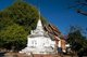 """Wat Prasat (วัดปราสาท) dates back at least as far as the 16th century CE, and is probably still older.<br/><br/>  The most important building in the temple complex is the old viharn, which dates from 1823 but was tastefully renovated in 1987. Built in traditional and distinctively Lan Na style, the viharn is built of skillfully-crafted teak wood panels on a whitewashed brick and stucco base. The main entrance, which naturally faces east, is reached by a low flight of steps flanked by naga balustrades. <br/><br/>  The interior of the temple is elegantly understated, with tall teak pillars supporting a low-slung, tiled Lan Na roof. Unusually, at the western end of the building where the altar would usually be, there is instead an elaborately decorated entrance to the short 'tunnel' leading to the contiguous chedi, the latter housing a large gilded Buddha image that is only partly visible from the viharn due to its size. <br/><br/>  A number of Buddha images sitting on raised pedestals flank the entrance to the tunnel. All but one are of stucco, but the image closest to the tunnel entrance, on the right hand pedestal, is of cast bronze and dates from 1590 during the reign of King Nawrathaminsaw (r. 1578-1607), the first Burmese ruler of Chiang Mai.<br/><br/>  King Mengrai founded the city of Chiang Mai (meaning """"new city"""") in 1296, and it succeeded Chiang Rai as capital of the Lanna kingdom. Chiang Mai sometimes written as """"Chiengmai"""" or """"Chiangmai"""", is the largest and most culturally significant city in northern Thailand."""
